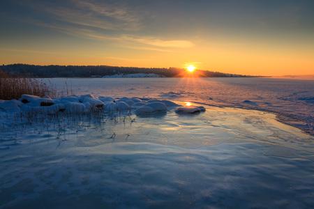Winter landscape with snow, frozen ocean, ice, blue sky at sunrise in Norway, Fredrikstad, Nature Reserve. This is an important area for birds and bird watchers in Norway. January. Stock Photo
