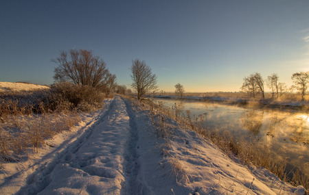 Winter landscape with snow, river, blue sky, road, sunshine, ice.