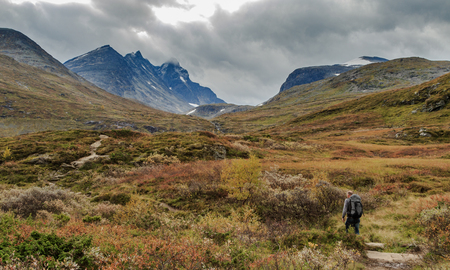 Man walks towards the mountains of Hurrungane in Jotunheimen, Norway