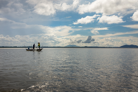 subsist: Two people fishing with net from a boat in Sarawak, Borneo