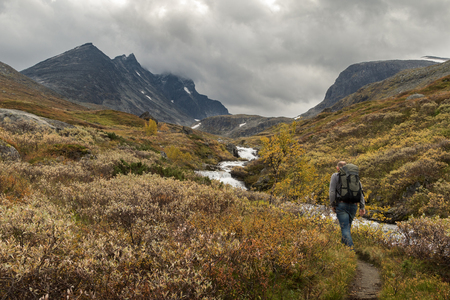 Man walking alone beside river stream towards the mountains of Hurrungane in Jotunheimen, Norway