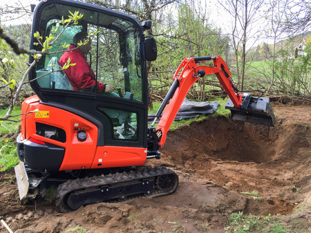 Small excavator with man inside, at work making garden pond Stock Photo