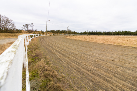 Empty race track for racing horses, sand track and white fence Stock Photo