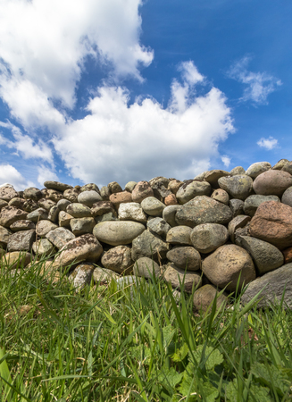 Old Stone wall with green grass in front and blue sky with clouds above, vertical image Stock Photo