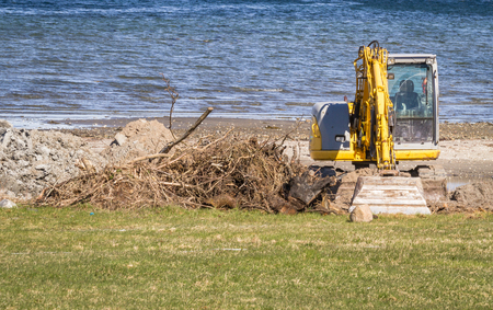 temporarily: excavator and a pile of sand in front of the ocean