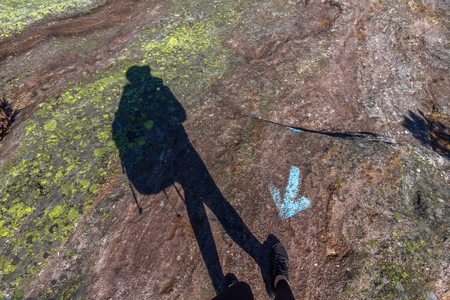 Human shadow walking in wrong direction, against blue arrow on rock