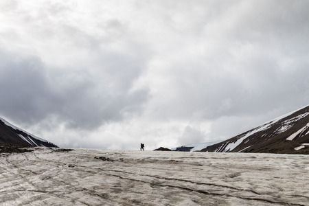 Man walking into the wild on a glacier in Svalbard Stock Photo