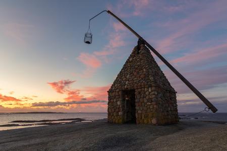 ende: Old lighthouse made of rocks, in beautiful sunrise at Verdens Ende in Vestfold Norway