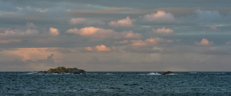 Sunrise with pink sky and clouds over the ocean and archipelago of Faerder National Park, Norway