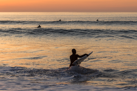Surfer carrying the surfboard into water with waves in the sunset Stock Photo