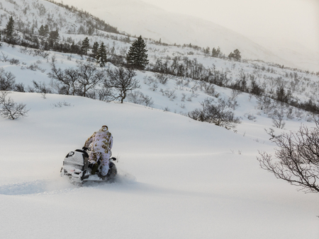 Man driving snowmobile in the snow Stock Photo
