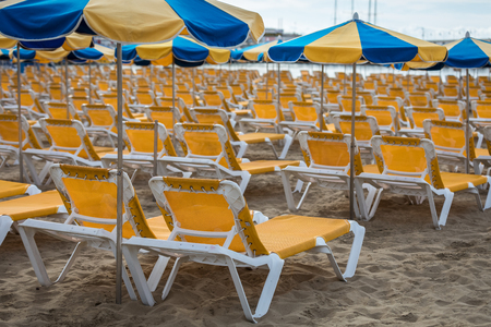Rows of yellow sunbeds with blue and yellow parasols at the beach Playa de Puerto Rico on the Canary Island
