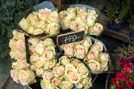 Vase of pink rose bouquets with price tag in the street