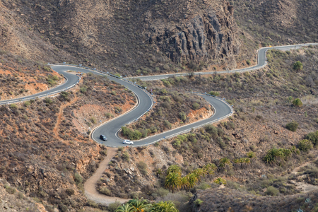 Curved winding road with two cars driving in the mountains in Gran Canaria