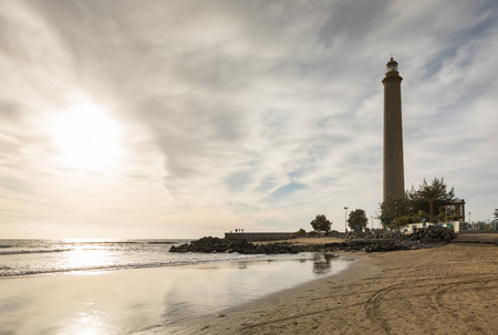 Horizontal shot of the beautiful beach in Maspalomas, with Faro de Maspalomas or Maspalomas lighthouse, in the background, Gran Canaria, Spain
