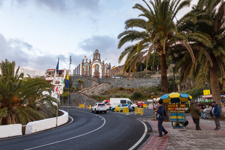 Santa Lucia, Gran Canaria in Spain - December 13, 2017: Street with people and cars, and the church in the back, at the special day of the Fiesta for the patron saint, Santa Lucia Editorial