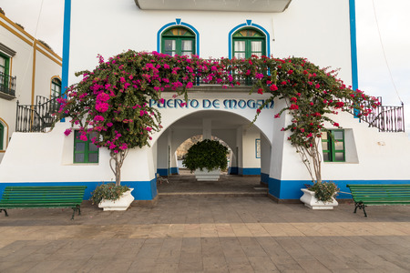 Puerto de Mogan, Gran Canaria in Spain - December 16, 2017: Puerto de Mogan, pink and red flowers growing over the arch at the ferry pier Editorial