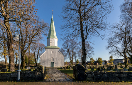 White wooden church seen from the side, trees, grass and blue sky in autumn, Kristiansand, Norway Reklamní fotografie - 93332352