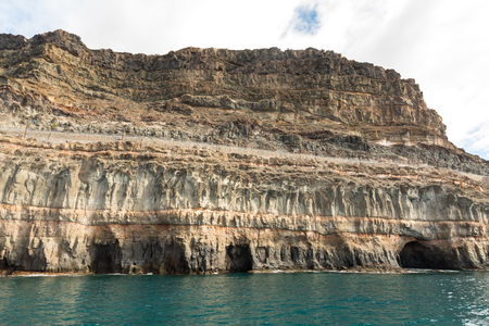 Gran Canaria, Canary Islands in Spain: Layers of volcanic rock. Strata. The powerful mountains at the coast between Puerto de Mogan and Puerto Rico. Stock Photo