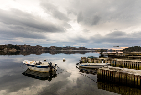 Forresfjorden, Karmoy in Norway - januray 10, 2018: A small motorboat resting in the water by a pier in the fjord Forresfjorden. Beautiful sky and blue light Editöryel