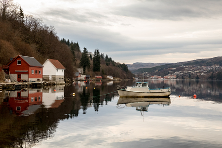 Forresfjorden, Karmoy in Norway - januray 10, 2018: A small motorboat resting in the water in the fjord Forresfjorden. Boat houses by the sea. Beautiful sky and blue light Editöryel