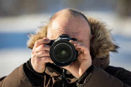 Norway, february 3, 2018: A male photographer in winter clothing is holding a Canon camera with the Canon 24-70mm 2,8 L II lens. Shallow depth of field, outdoors in snowy winter.