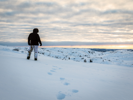 Alone man walking in snow in the wilderness at sunrise Stock Photo