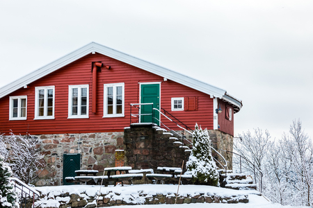 Odderoya in Kristiansand, Norway - January 17, 2018: Krutthuset, the old, red powder house from 1697. Winter, snow on the ground.
