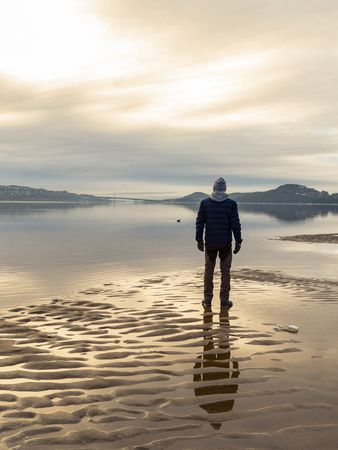 Man standing at the beach, reflections of the man in the water. Calm sea, mist and fog. Hamresanden, Kristiansand, Norway Stock Photo