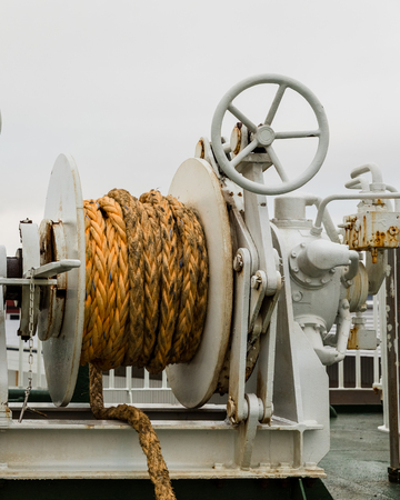 Winch with orange rope on a ferry, white cloudy backgrond