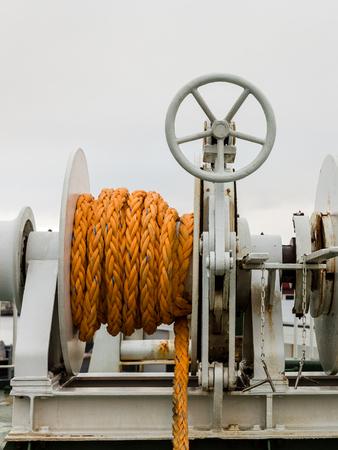 Treuil avec corde orange sur un ferry, backgrond nuageux blanc