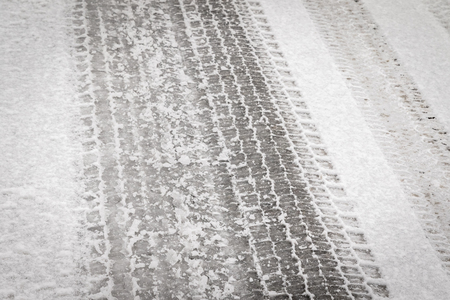 background texture of asphalt road covered with snow and tire tracks