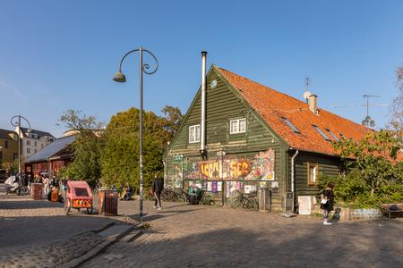COPENHAGEN, DENMARK - October 2018: Street with buildings and people in Freetown Christiania, a self-proclaimed autonomous neighbourhood in Copenhagen.