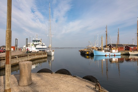 Holbaek, DENMARK - October 2018: The harbour with ferry terminal and beautiful old sail boats at the bay in Holbaek, a small town in Zealand, Denmark. Editöryel