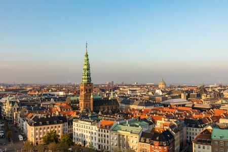 Copenhagen skyline in evening light. Copenhagen old town and copper spiel of Nikolaj Church. City streets and danish house roofs. High angle view from Christiansborg palace.
