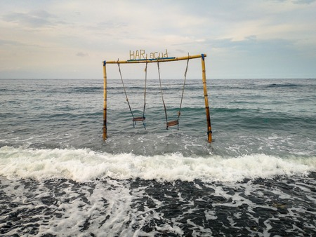Double swing in the ocean at the beach in Amed village in Bali Indonesia