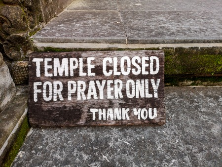 Sign: Temple closed for prayer only. Old wooden board with white letters. Stock Photo