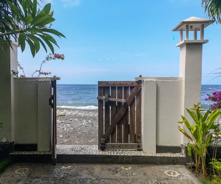 Wooden gate open towards the Amed Beach and the Bali Sea
