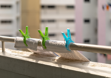 Plastic Clothes Clips on the Railing. Laundry Hooks with wash cloths. Apartment buildings in the background.