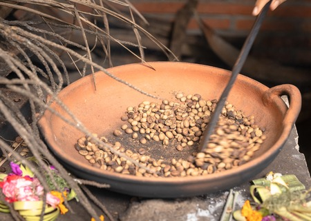 Traditional coffee beans roasting in a pan, hand held spoon moves the beans. Bali tradition. Stock Photo