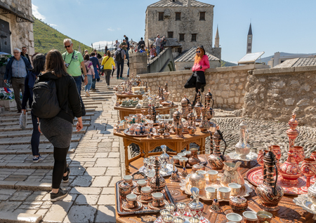 Mostar, Bosnia and Herzegovina - April, 2019: Mostar old town. Tourists at the market by the famous Stari Most bridge.