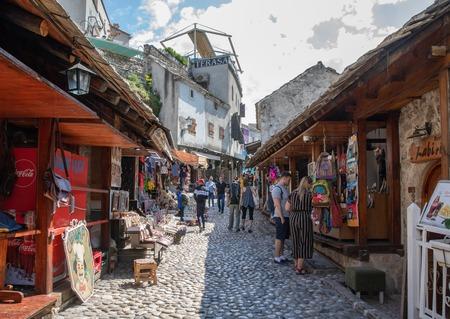 Mostar, Bosnia and Herzegovina - April, 2019: Mostar old town. Tourists at the market street.