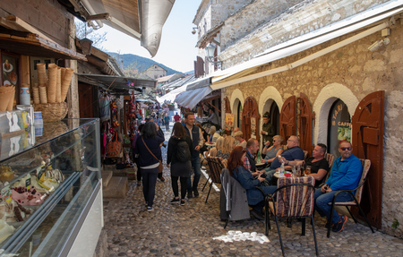 Mostar, Bosnia and Herzegovina - April, 2019: Mostar old town, tourists in the market with restaurants and shops. Editöryel