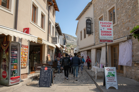 Mostar, Bosnia and Herzegovina - April, 2019: Mostar old town. Tourists walking into the market street.