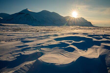 Arctic winter landscape with snow covered mountains at Kapp Ekholm, Svalbard, Norway, backlit Banque d'images - 133061433