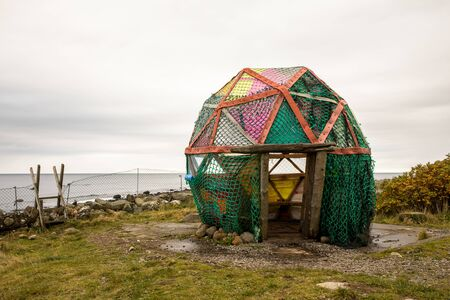 Cabin by the ocean made by plastic from the ocean, at Borhaug, Norway. Landscape by the sea.