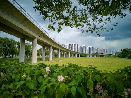 Train bridge in Jurong, Singapore, with green vegetation in front and blue sky in background Stock Photo