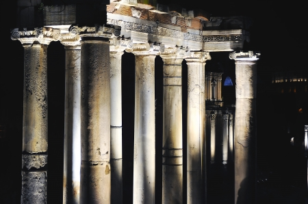 Roman columns light up in the dark night Stock Photo