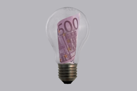 The concepts of money and energy are encased in a light bulb Stock Photo - 17564454