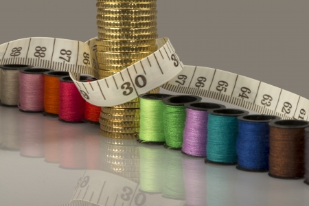 Tailoring costs represented by coins, threads and meters Stock Photo